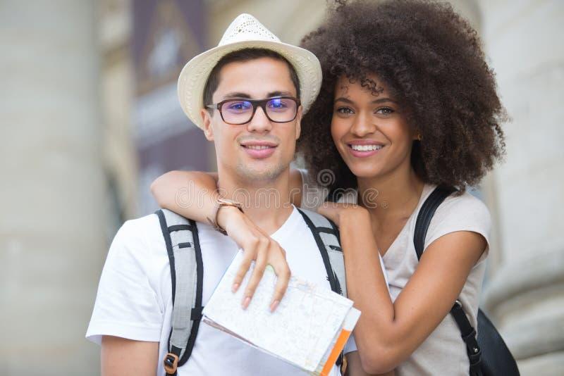 Pares turísticos jovenes hermosos que presentan en ciudad foto de archivo libre de regalías