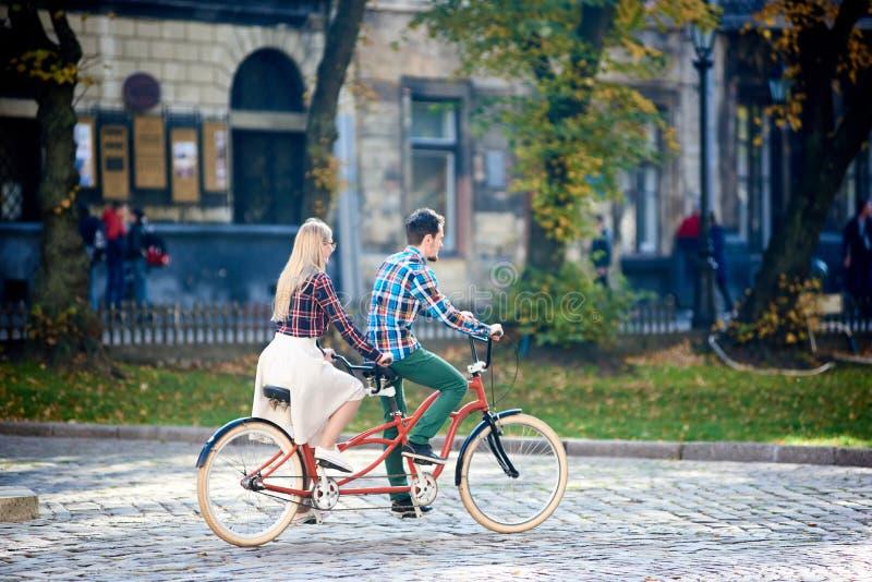 Pares turísticos jovenes, hombre hermoso y mujer bastante rubia montando la bicicleta en tándem a lo largo de la calle de la ciud fotos de archivo libres de regalías