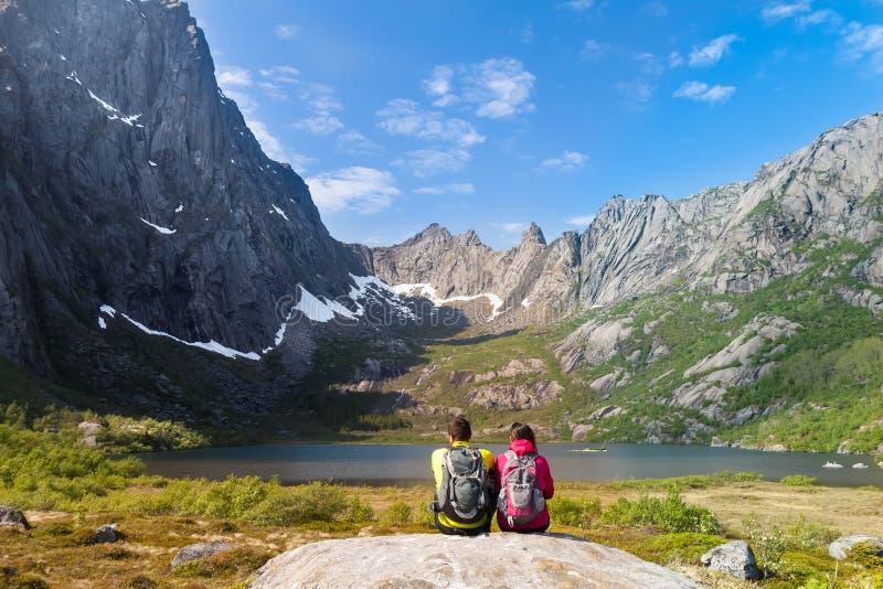 Pares turísticos jovenes que se sientan en cercano de piedra imagen de archivo