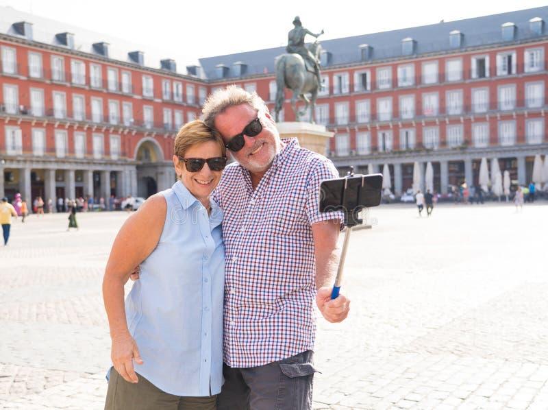 Pares turísticos mayores jubilados felices que se colocan que toman Selfie en a fotos de archivo libres de regalías