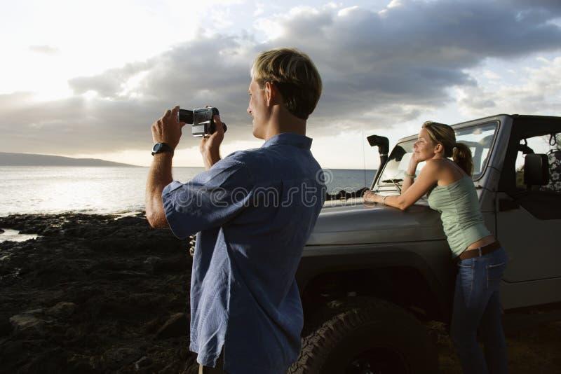 Pares turísticos que disfrutan de una puesta del sol de la playa fotografía de archivo libre de regalías