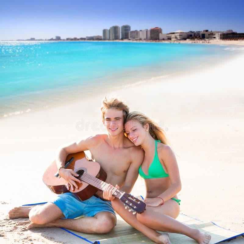 Pares turísticos rubios que tocan la guitarra en la playa fotos de archivo libres de regalías