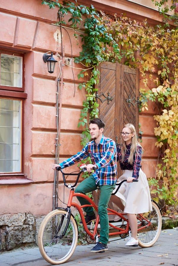 Pares tur?sticos jovenes, hombre hermoso y mujer bastante rubia montando la bicicleta en t?ndem a lo largo de la calle de la ciud imagenes de archivo