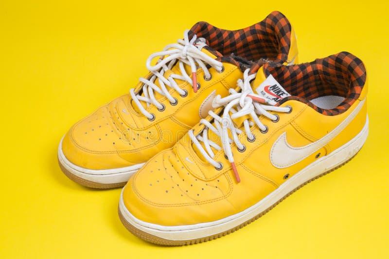 Pares usados de zapatillas de deporte amarillas de Nike Air Force en fondo amarillo foto de archivo
