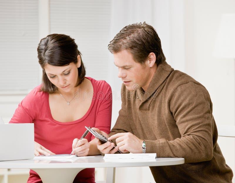 Pares usando a calculadora para pagar contas mensais imagens de stock royalty free