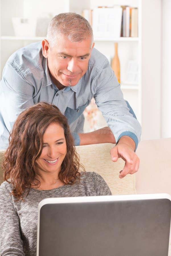 Pares usando el ordenador portátil en casa imagen de archivo