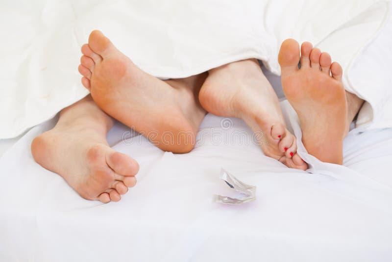 Pares usando la contracepción en cama imagen de archivo