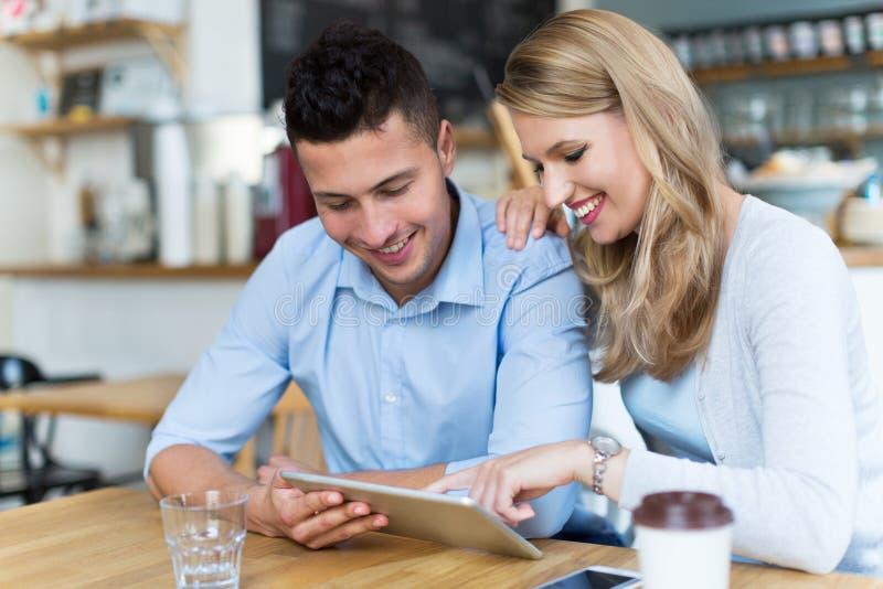 Pares usando la tableta digital en café imagen de archivo