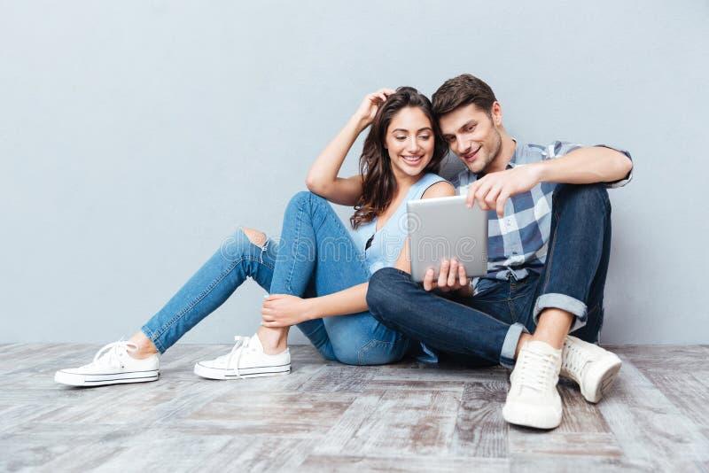 Pares usando la tableta que se sienta en el piso en casa imagen de archivo