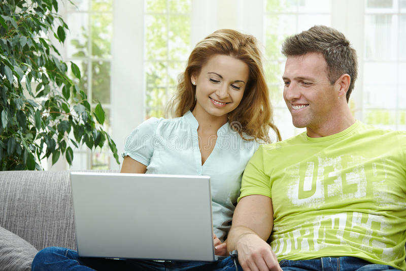 Pares usando o computador portátil fotografia de stock royalty free