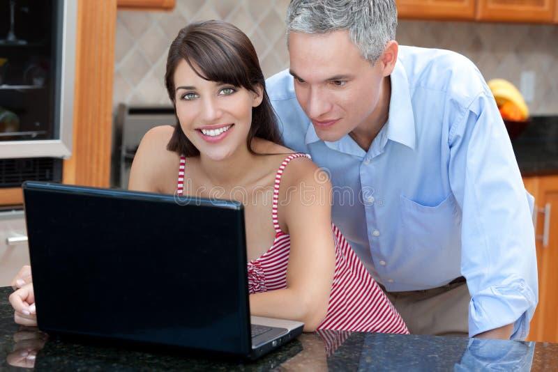 Pares usando o computador portátil na cozinha imagens de stock