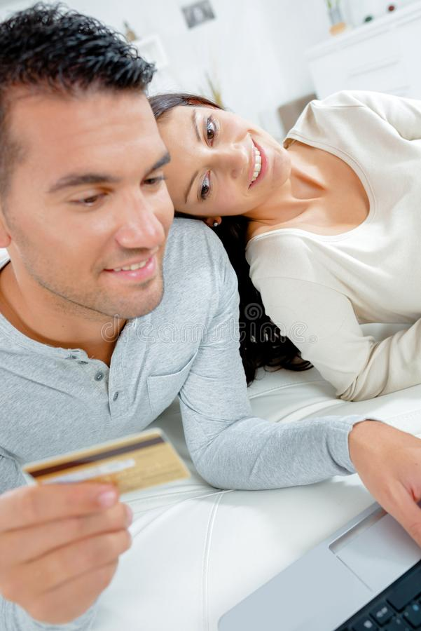 Pares usando o portátil e guardando o cartão do pagamento fotografia de stock royalty free
