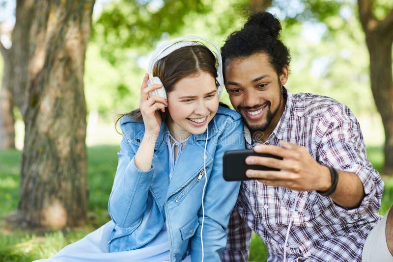 Pares usando Smartphone en verano fotografía de archivo libre de regalías