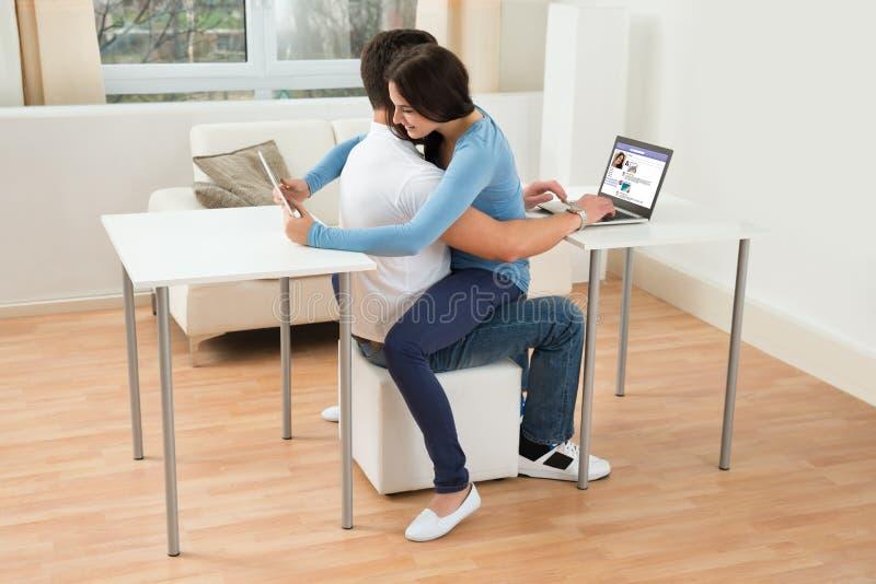 Pares usando a tabuleta e o portátil digitais fotografia de stock