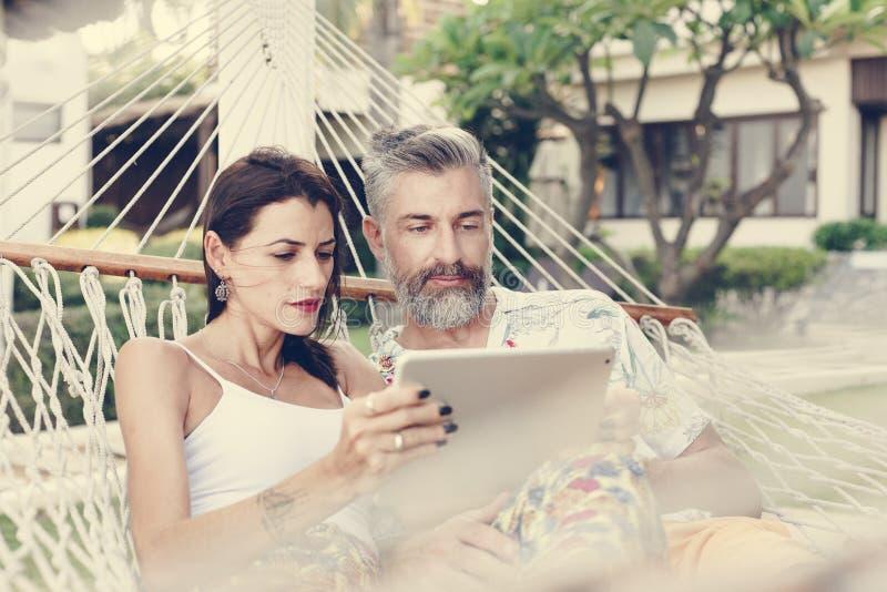 Pares usando una tableta en una hamaca fotos de archivo