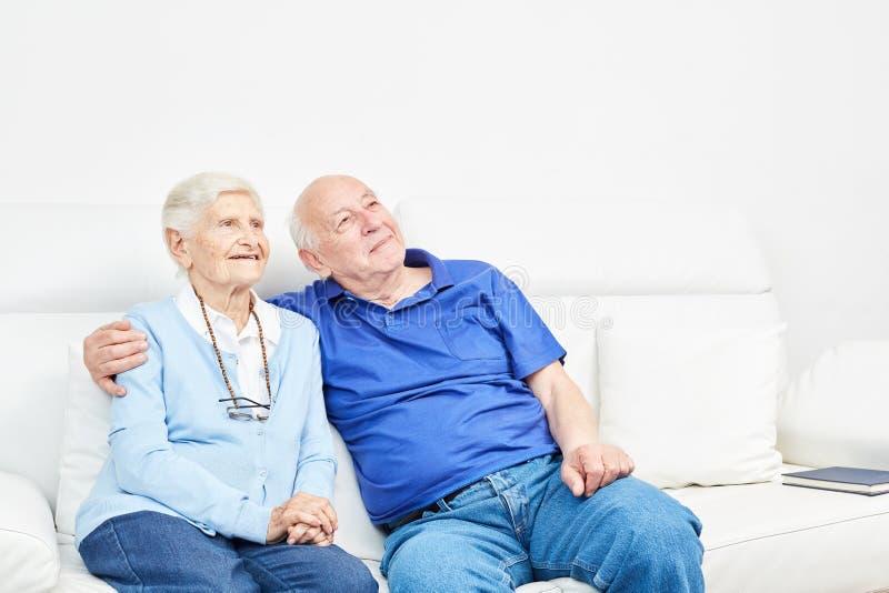 Pares velhos felizes no sofá foto de stock royalty free