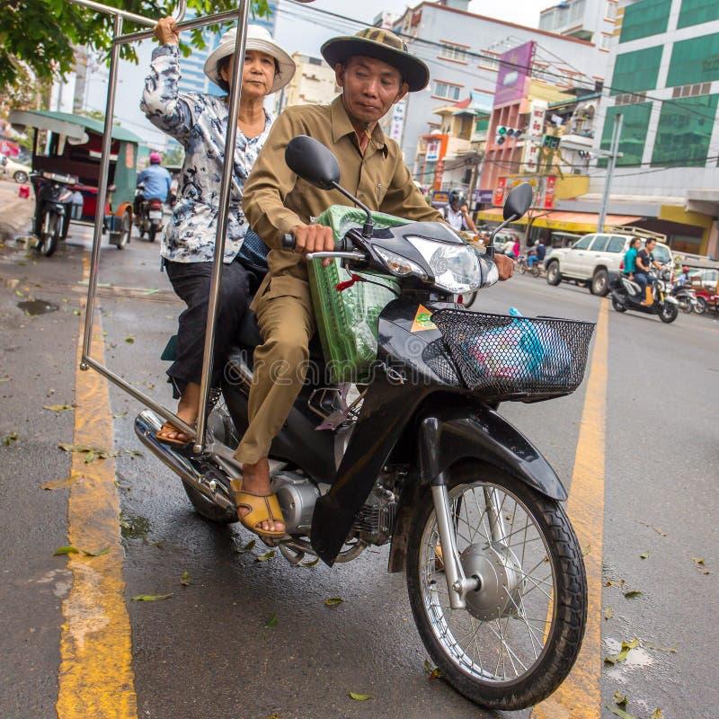 Pares velhos que conduzem seu velomotor em Phnom Penh imagens de stock royalty free