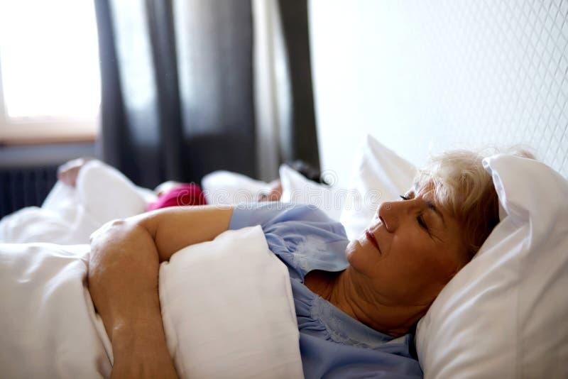 Pares velhos que dormem na cama imagens de stock