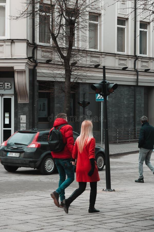 Pares vestidos no vermelho brilhante que anda na cidade imagens de stock