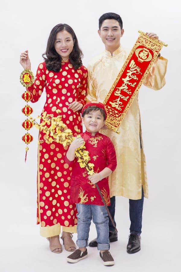 Pares vietnamitas que llevan a cabo el artículo de la buena suerte por Año Nuevo fotografía de archivo