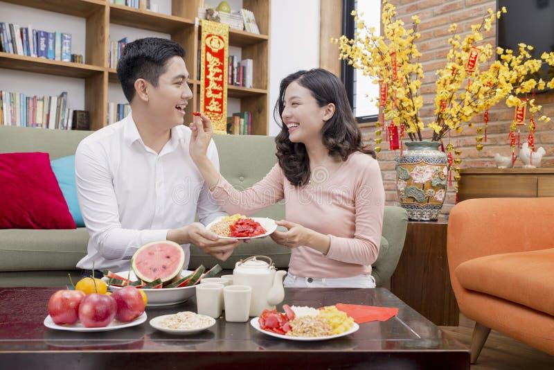 Pares vietnamitas que llevan a cabo el artículo de la buena suerte por Año Nuevo fotos de archivo