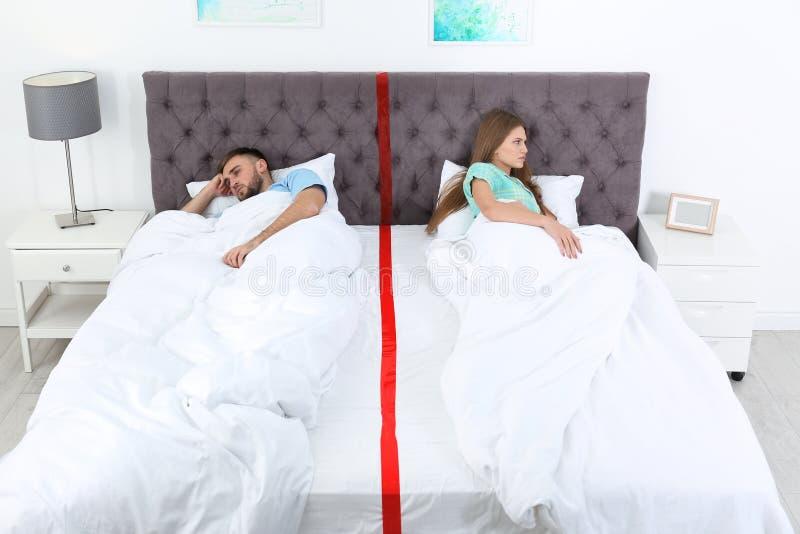 Pares virados com os problemas do relacionamento que encontram-se separadamente na cama foto de stock royalty free