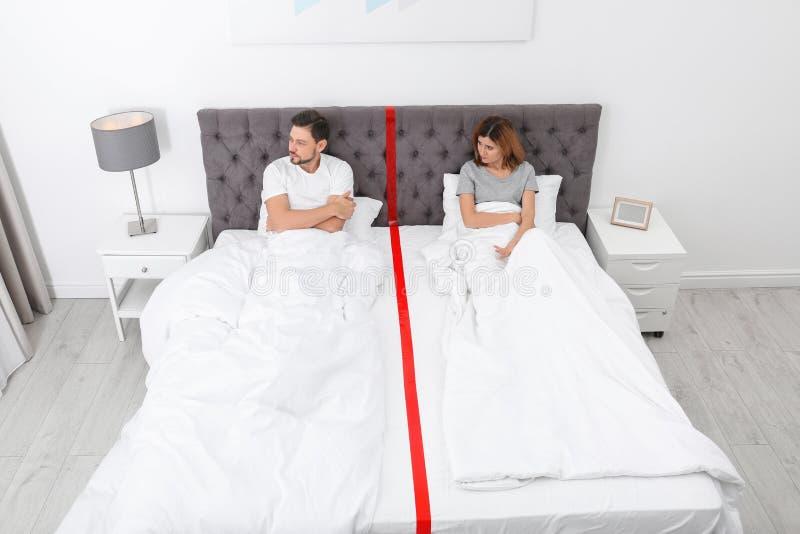 Pares virados com os problemas do relacionamento que encontram-se separadamente na cama fotografia de stock royalty free