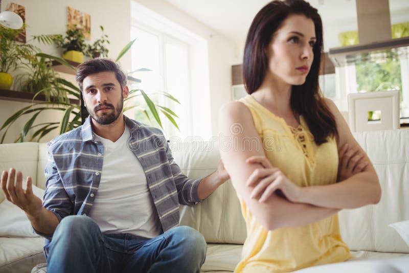 Pares virados que discutem um com o otro no sofá fotografia de stock