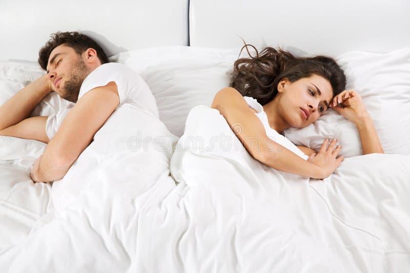Pares virados que encontram-se de lado a lado na cama fotografia de stock