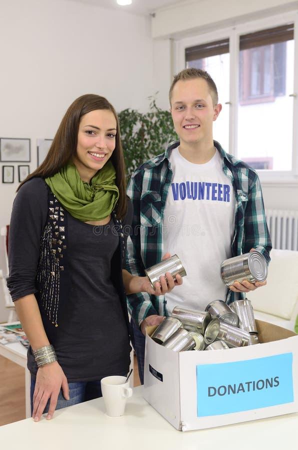 Pares voluntarios de los jóvenes con el rectángulo de la donación del alimento