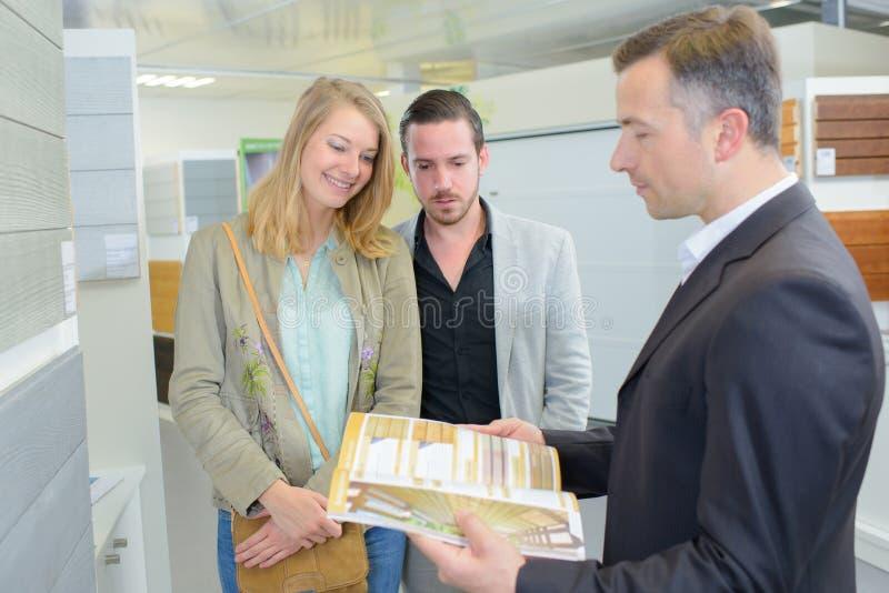 Pares y agente jovenes con los documentos comerciales imagenes de archivo