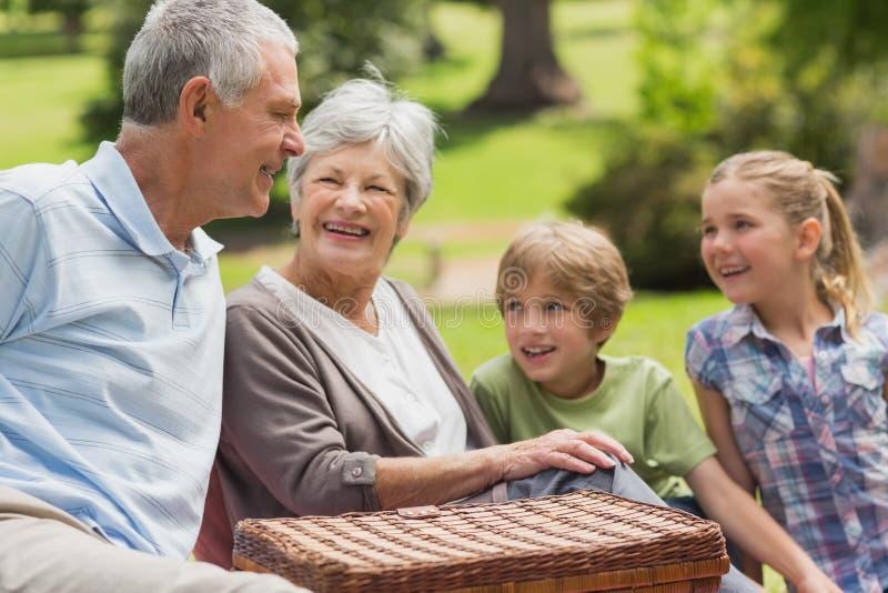Pares y nietos mayores sonrientes en el parque foto de archivo libre de regalías