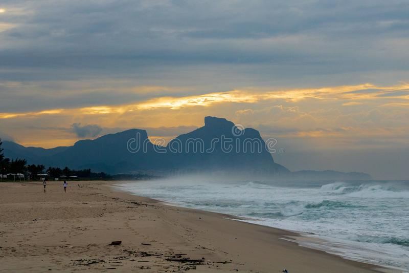 Pares y perro que corren en la playa de Barra da Tijuca en un amanecer hermoso con la piedra de Gavea en el fondo - Rio de Jane fotografía de archivo