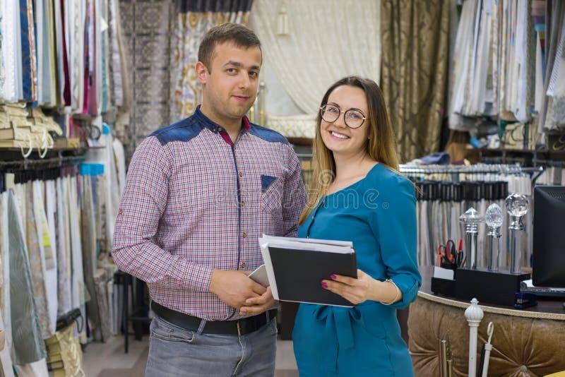 Paret är mannen och kvinnan, ägare av litet familjeföretag Show-rum shoppar av hem- textiler, tyger, gardiner royaltyfria foton
