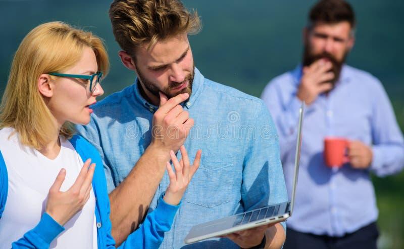 Paret arbetar illvilja av kaffeavbrottet Arbetsnarkomanbegrepp Kollegor som arbetar bärbara datorn, framstickande som röker medan arkivfoto