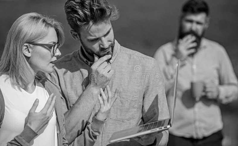 Paret arbetar illvilja av kaffeavbrottet Arbetsnarkomanbegrepp Kollegor som arbetar bärbara datorn, framstickande som röker medan royaltyfri foto