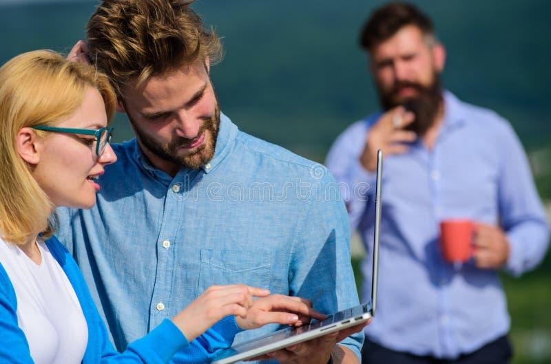 Paret arbetar illvilja av kaffeavbrottet Kollegor med bärbara datorn arbetar den utomhus- soliga dagen, naturbakgrund kollegor royaltyfri foto