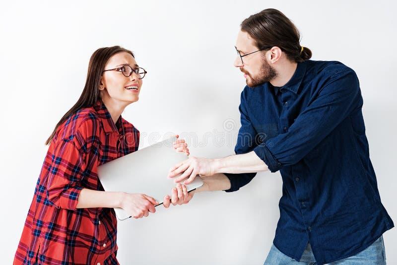 Paret argumenterar om besittning av den moderna datoren fotografering för bildbyråer