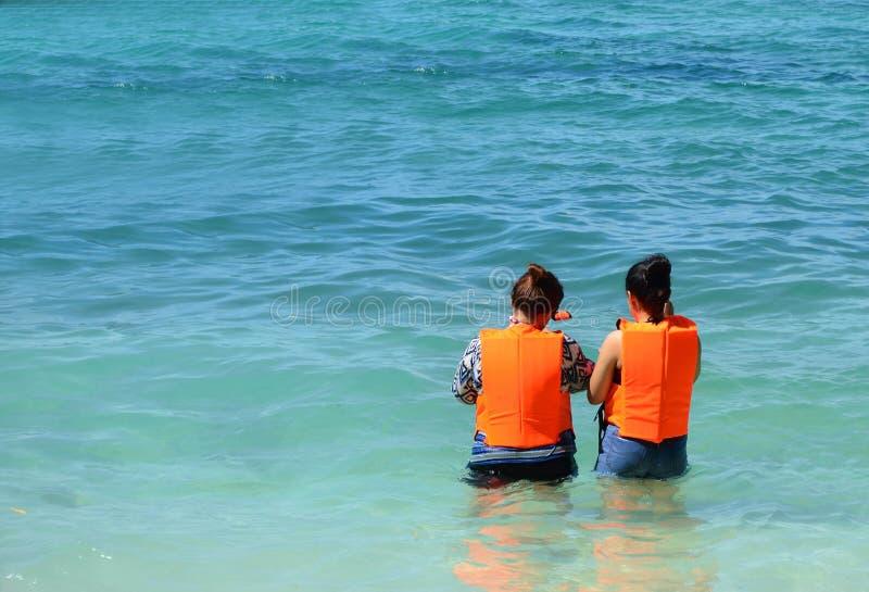 Paret av den unga asiatiska kvinnan ska dyka i det blåa havet arkivbilder