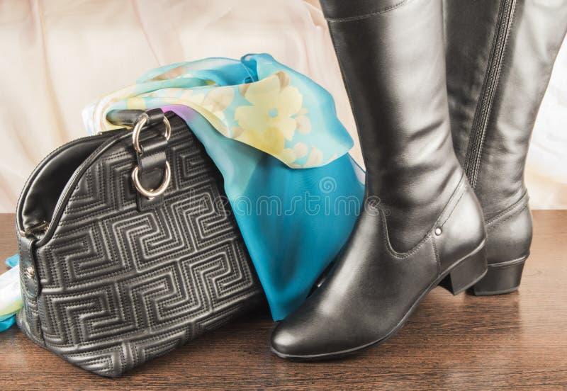 Paret av kvinnligsvart startar och handväskan med den blåa sjalen arkivbilder