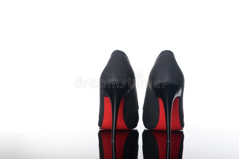 paret av spetsiga kvinnaskor med svart sular röda höga häl royaltyfri bild