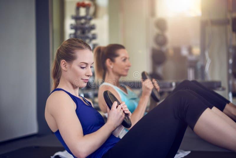 Paret av unga vuxna kvinnor som gör den buk- muskeln, övar arkivbild