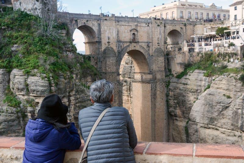 Paret beundrar sikten av den spanska staden av Ronda Den berömda Puenten Nuevo är en ny bro över Guadaleven? n-flod över arkivfoto
