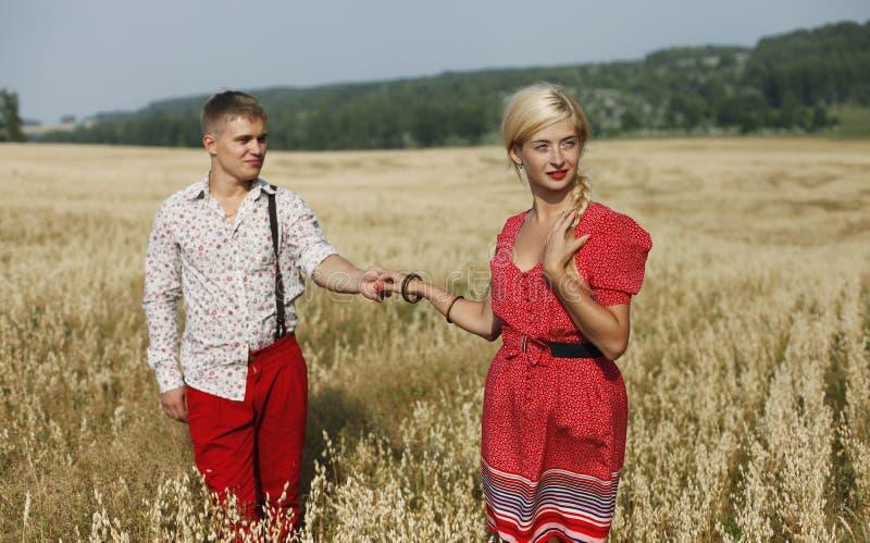 Paret går till och med ett fält av mogna öron av vete arkivfoton