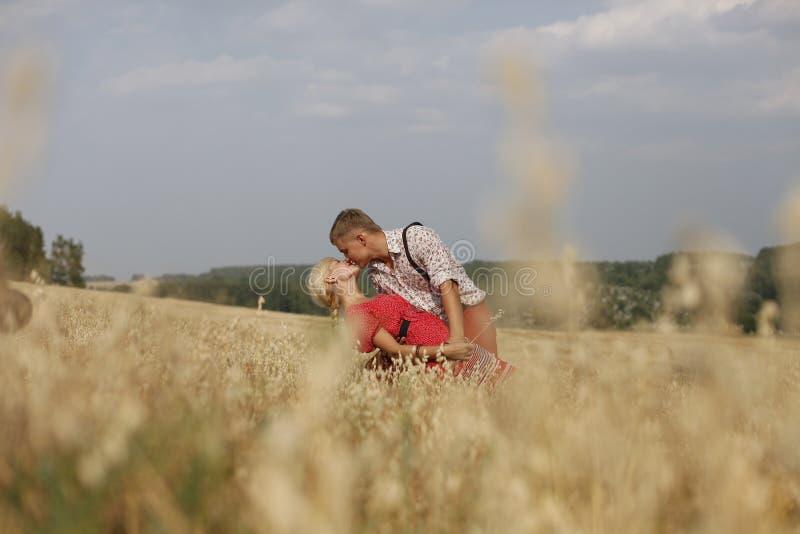 Paret går till och med ett fält av mogna öron av vete fotografering för bildbyråer