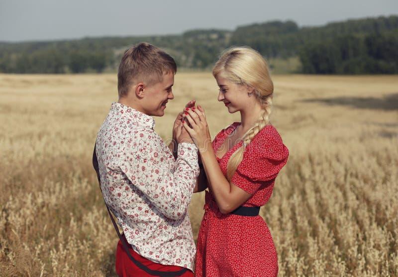Paret går till och med ett fält av mogna öron av vete arkivbilder