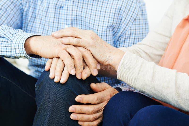 paret hands holdingpensionären arkivfoto