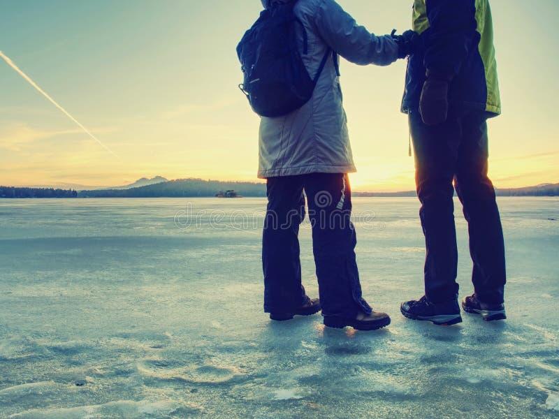 Paret har gyckel under vinter går på is av den djupfrysta sjön royaltyfri bild