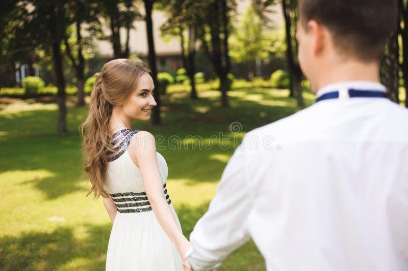 Paret i bröllopdress är i händerna mot bakgrunden av fältet på solnedgången, bruden och brudgummen arkivbild