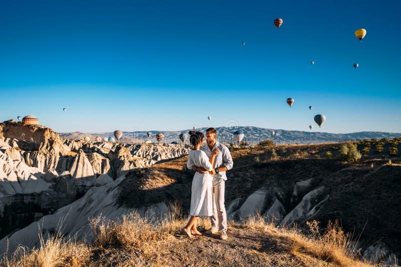 Paret möter gryningen Mannen föreslogg till flickan Familjtur till Turkiet Koppla ihop på ballongfestivalen Br?llopsresatur arkivfoto